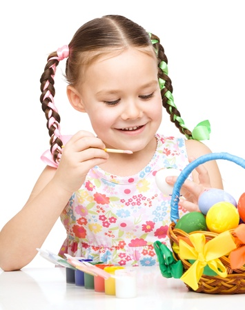 Little girl preparing eggs for Easter, isolated over white photo