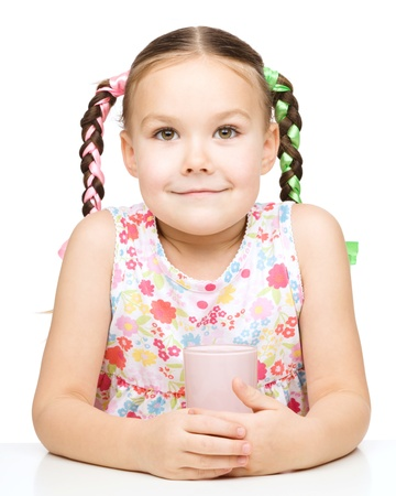 Cute little girl drinks milk, isolated over white photo