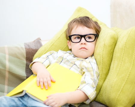 Cute little child holding a book and wearing glasses while laying on couch photo