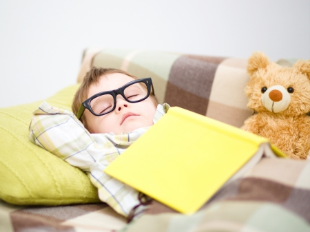 Cute little boy is sleeping in front of his teddy bears wearing glasses and put off a big book Stock Photo - 18441268
