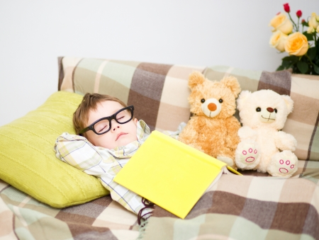 Cute little boy is sleeping in front of his teddy bears wearing glasses and put off a big book photo