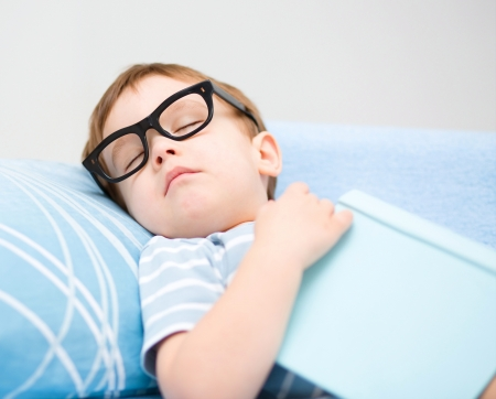 Cute little boy is sleeping while wearing glasses and put off a big book Stock Photo - 18495479