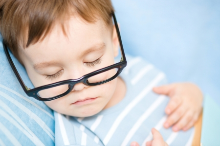 Cute little boy is sleeping while wearing glasses and put off his book photo