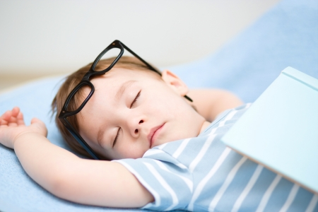 Cute little boy is sleeping while wearing glasses and put off his book Stock Photo - 18503026