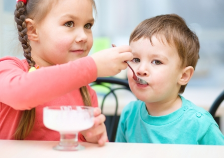 Girl is feeding his little brother with ice-cream in parlor photo