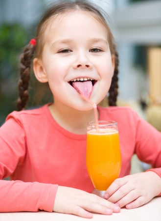 Little girl is drinking orange juice using straw Stock Photo - 18503090