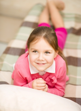 child in bed: Portrait of a cute little girl on couch Stock Photo