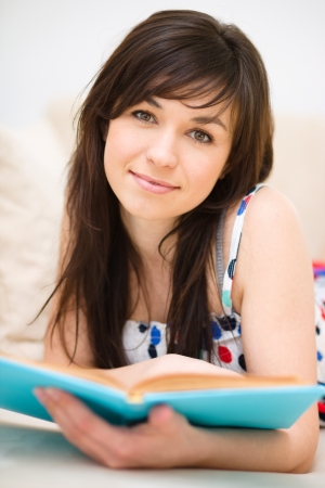 one story: Young woman is reading book while sitting on a couch, indoor shoot Stock Photo