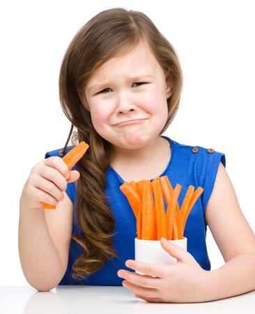 Cute little girl is eating carrot and feel very unhappy about it, isolated over white photo