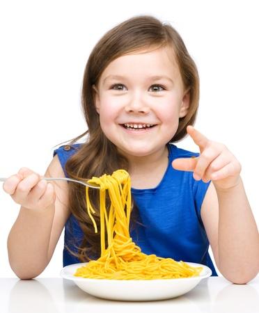 Little girl is eating spaghetti, isolated over white Imagens - 18693239