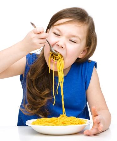 Little girl is eating spaghetti, isolated over white