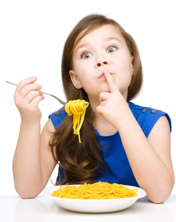 Little girl is eating spaghetti while showing hush gesture, isolated over white Imagens