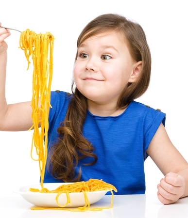 over eating: Little girl is eating spaghetti, isolated over white