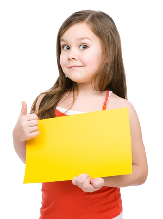 Little girl is holding blank yellow banner and showing thumb up gesture, isolated over white Banque d'images