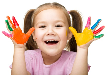 messy kids: Portrait of a cute cheerful girl showing her hands painted in bright colors, isolated over white