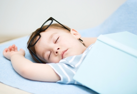 Cute little boy is sleeping while wearing glasses and put off a big book photo