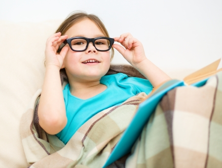 Cute little girl is reading book while sitting on a couch, indoor shoot photo