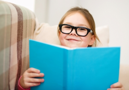 enlightenment: Cute little girl is reading book while sitting on a couch, indoor shoot