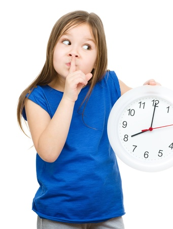 Little girl is holding big clock and showing hush gesture, isolated over white photo