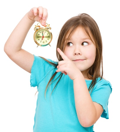 Little girl is holding small alarm clock and pointing at it, isolated over white