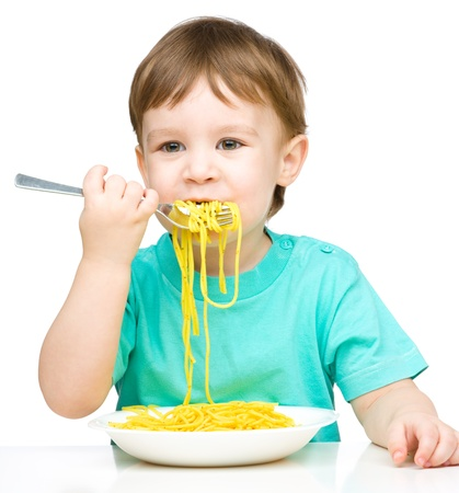 over eating: Little boy is eating spaghetti using fork, isolated over white