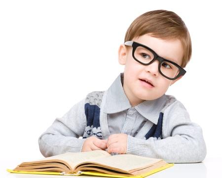 42171dc8ac9749  19028020 - Schattige kleine kind te spelen met boek en bril terwijl zittend  aan tafel