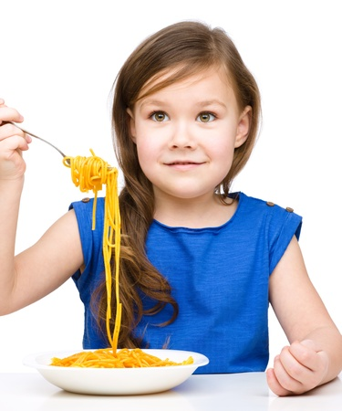 Little girl is eating spaghetti, isolated over white photo