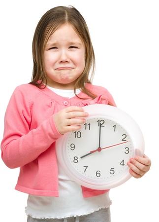 niño llorando: La niña está sosteniendo un reloj grande y mostrando gesto infeliz, aislado más de blanco