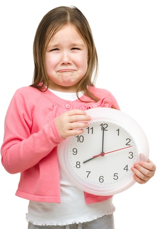 crying child: Little girl is holding big clock and showing unhappy grimace, isolated over white