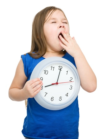 Little girl is holding big clock while yawning, isolated over white photo