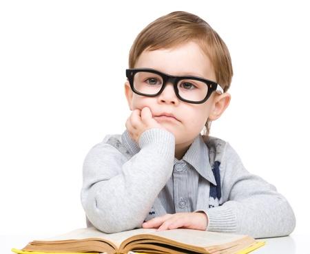 bambini pensierosi: Carino piccolo bambino gioca con il libro e con gli occhiali, mentre seduti a tavola, isolato su bianco