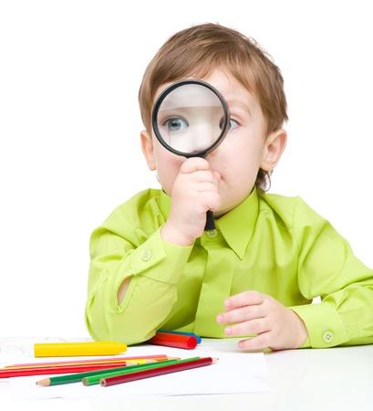 かわいい男の子は白で分離された拡大鏡を通して見る 写真素材