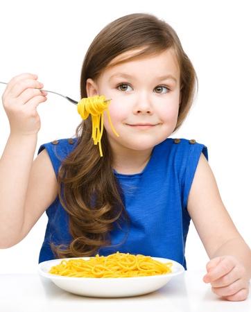 macarrones: La niña está comiendo espaguetis, aislados en blanco