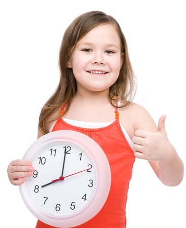 Little girl is holding big clock and showing thumb up gesture, isolated over white photo