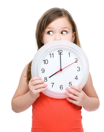 Little girl is holding big clock, isolated over white Zdjęcie Seryjne