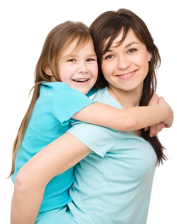 mom and child: Portrait of a happy daughter piggyback ride her mother, isolated over white