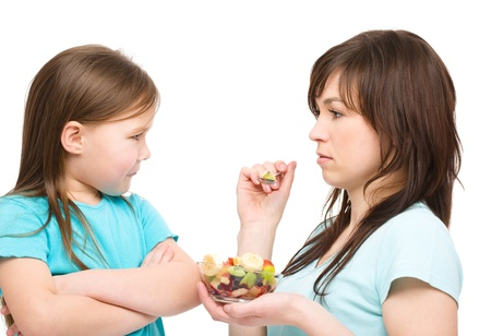 feed up: Mother is trying to feed her daughter with fruit salad, isolated over white