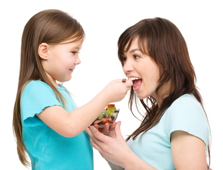 Daughter is feeding her mother with fruit salad, isolated over white photo