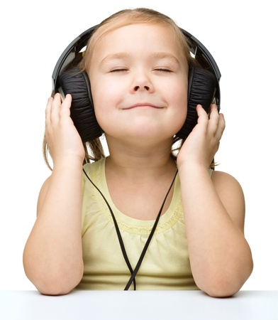 Cute little girl is enjoying music using headphones and closed her eyes, isolated over white