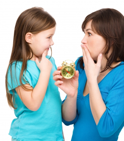 dismayed: Little girl and her mother are anxious about time, isolated over white
