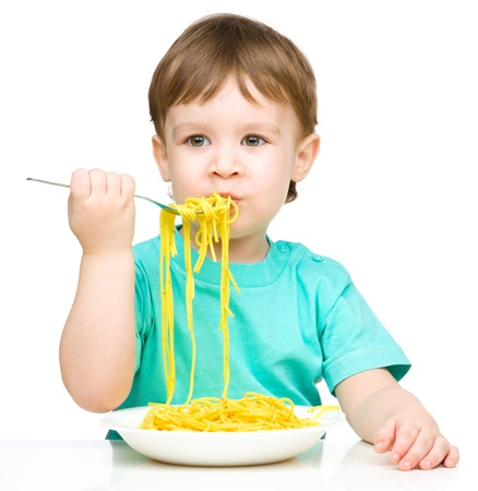 eating noodles: Little boy is eating spaghetti using fork, isolated over white