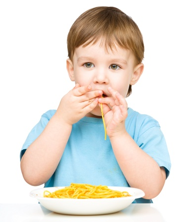 Little boy is eating spaghetti using both hands, isolated over white photo