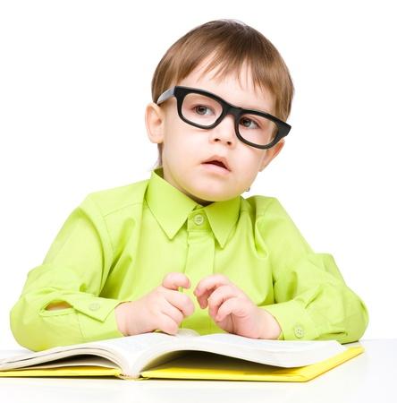 bambini pensierosi: Gioco bambino piccolo carino con libro e occhiali seduti a tavola, isolato su bianco Archivio Fotografico