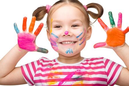 niños dibujando: Retrato de una linda chica alegre que muestra sus manos pintadas de colores brillantes, aislados en blanco Foto de archivo