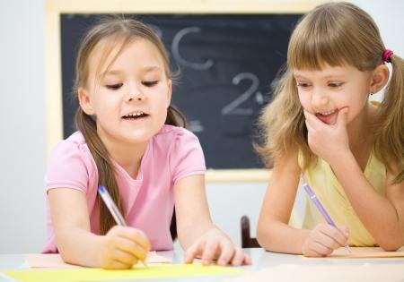 niños escribiendo: Ni?as lindas est?n escribiendo con un l?piz en preescolar