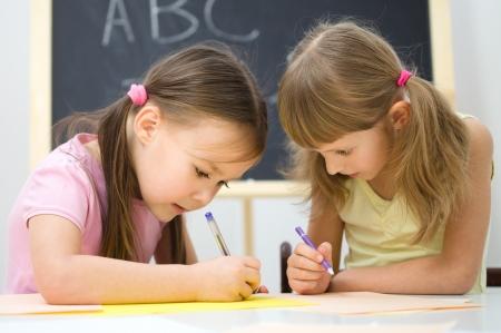kids class: Cute little girls are writing using a pen in preschool
