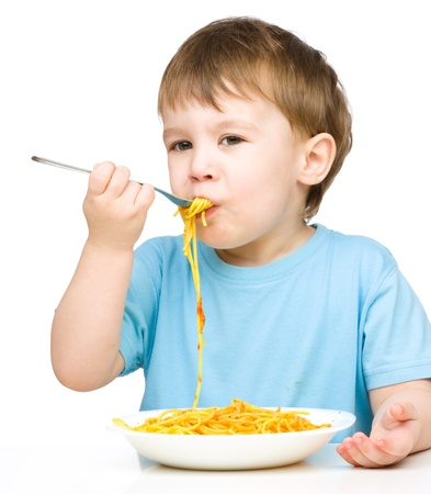Little boy is eating spaghetti using fork, isolated over white photo