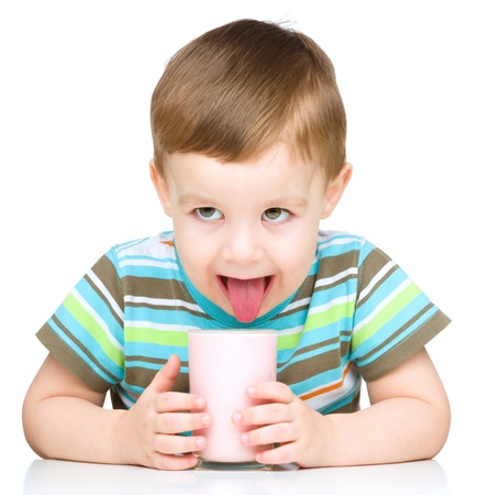 Cute little boy is dipping his tongue in the glass of milk, isolated over white photo