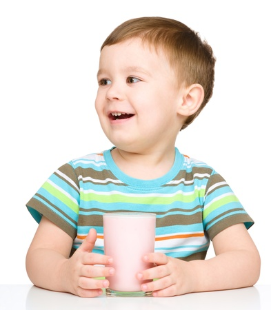 Cute little boy with a glass of milk, isolated over white photo