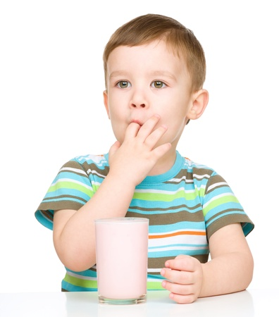 little finger: Cute little boy with a glass of milk sucking his finger, isolated over white